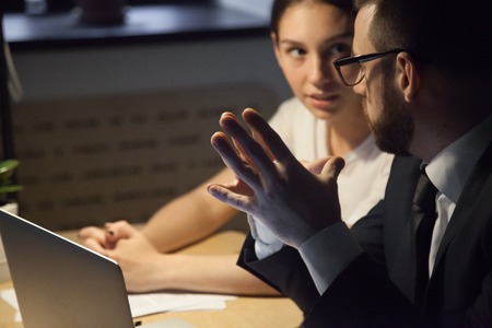 Male worker keeping hands up with fingertips put together, listening to female colleague talking, discussing company strategy, negotiating about business issue, working late hours in office Stock Photo