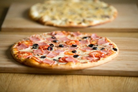 Tasty hot baked pizzas with ham or bacon, tomatoes, olives and cheese on wooden boards on restaurant table, food delivery service for delicious italian meal, pizzeria place concept, close up view