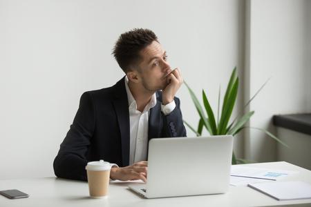 職場でラップトップで働く退屈な感じのスーツを着た退屈な疲れたミレニアル世代のビジネスマン、ぼんやりした従業員の思考や退屈な単調なオフィスルーチン、モチベーションなし、アイデアの概念の欠如