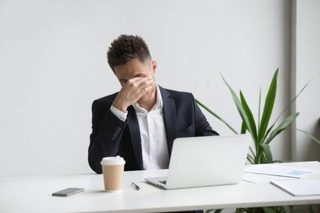 Frustrated stressed businessman feeling tired of computer work sitting at workplace, exhausted man in suit suffers from eye strain or blurry vision problem after long laptop use, eyes fatigue concept Stock fotó - 102258645