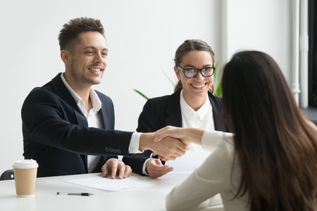 Smiling hr manager and hired female applicant won job interview shaking hands, friendly executive handshaking successful vacancy candidate offering employment contract, welcoming new worker concept Фото со стока