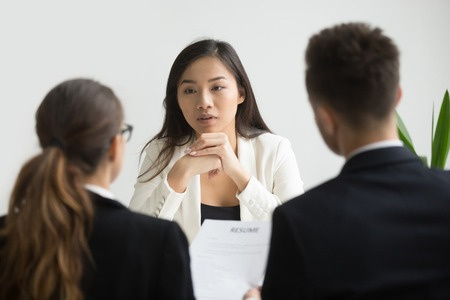 Confident asian female applicant convincing hr managers to hire her at job interview, young skilled chinese professional candidate talking to recruiters making first impression, employment concept