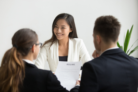 Confident millennial asian applicant smiling at job interview, happy beautiful chinese candidate or self-assured seeker being interviewed by hr managers, good performance and first impression concept Foto de archivo - 102258668