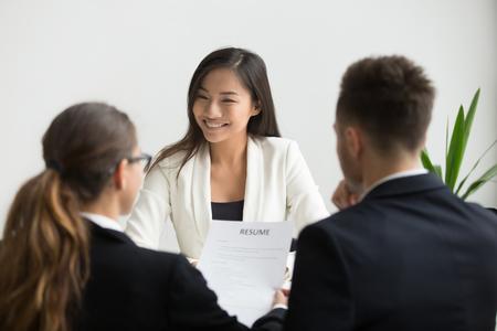 Selbstbewusster tausendjähriger asiatischer Bewerber, der beim Vorstellungsgespräch lächelt, glücklicher schöner chinesischer Kandidat oder selbstbewusster Sucher, der von Personalmanagern interviewt wird, gute Leistung und Konzept des ersten Eindrucks