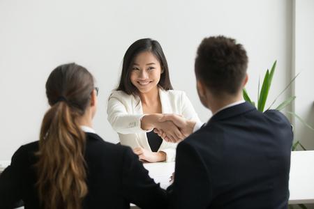 Glücklicher tausendjähriger asiatischer Bewerber, der angeheuert wird, Händeschütteln von hr, Arbeitgeberhändeschütteln erfolgreicher lächelnder chinesischer Kandidat, der mit Vorstellungsgesprächsgewinn gratuliert, bietet Arbeitsvertragskonzept an Standard-Bild
