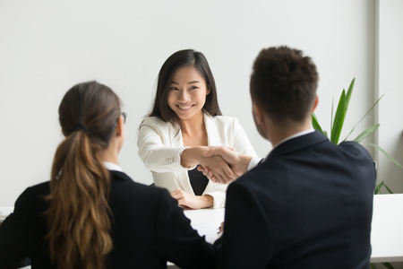 Happy millennial asian applicant getting hired shaking hand of hr, employer handshaking successful smiling chinese candidate congratulating with job interview win offering employment contract concept Banque d'images - 102258669