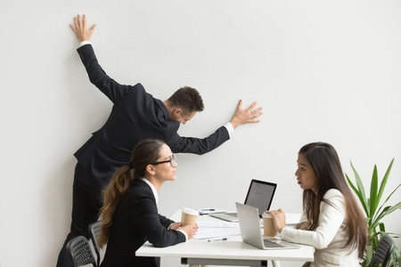 Businessman getting bored of dull work at team meeting, silly office worker leaning on wall pretending funny escape tired of boring routine dreaming of vacation while colleagues having discussion