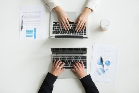 Collega's werken samen online samen met behulp van computers op kantoor tafel Bureau, vrouwelijke en mannelijke handen van twee kantoorpersoneel typen op laptops, mensen en apparaten concept, close-up bovenaanzicht Stockfoto