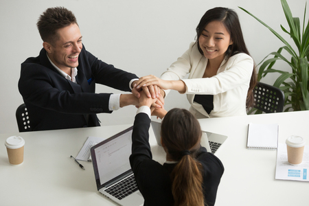 Happy smiling diverse team join hands together at group meeting, asian and caucasian millennial business people celebrate success achievement victory, promising loyalty support in teamwork, top view