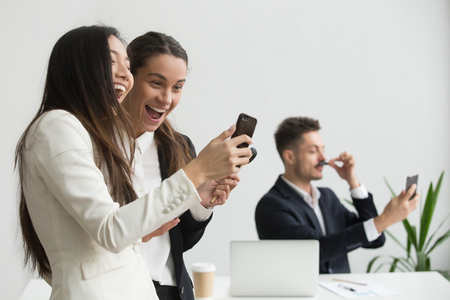 Diverse female colleagues laughing having fun with smartphone in office while male coworker taking silly selfie, excited multi-ethnic business people watching funny online video or using mobile apps