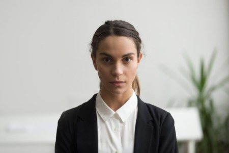 Serious young woman business leader in suit looking at camera, confident strict female manager, boss or company executive posing in office, millennial self-assured professional head shot portrait Stock Photo