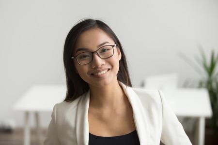 Lächelnde asiatische Frau in den Gläsern für die Sehkorrektur, die Kamera, glücklichen freundlichen chinesischen Studenten oder Angestellten betrachtet, der im Büro, professionelles Kopfschussporträt der tausendjährigen japanischen Frau aufwirft Standard-Bild