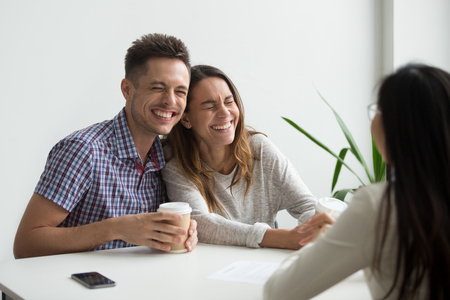 Happy couple clients laughing at funny joke meeting realtor, mortgage insurance broker or consultant, cheerful happy family customers having fun planning to sign contract buying services, taking loan