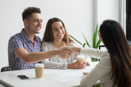Smiling millennial couple handshaking realtor or advisor making investment deal ready to sign mortgage contract, satisfied happy customers and broker or lawyer shaking hands buying insurance services