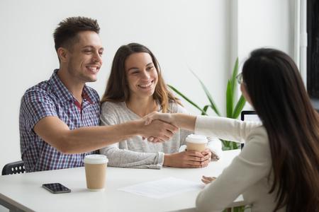 Uśmiechnięta para milenialsów, uścisk dłoni pośrednika lub doradcy, przygotowująca transakcję inwestycyjną do podpisania umowy o kredyt hipoteczny, zadowoleni zadowoleni klienci oraz broker lub prawnik ściskający ręce kupując usługi ubezpieczeniowe