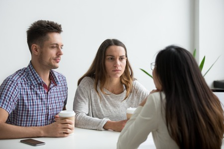 Doubtful distrustful customers couple looking suspicious worrying of being deceived listening to fraudster offering bad fraud deal, lawyer consulting skeptical millennial couple about legal fight