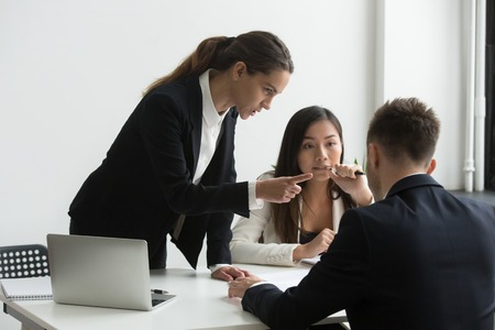 Angry businesswoman pointing finger threatens colleague at diverse team meeting, dissatisfied female executive blaming male employee of failure showing disrespect, gender hate discrimination concept Stok Fotoğraf - 102258709