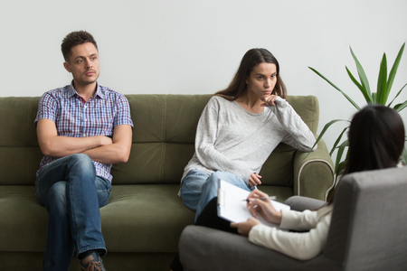Unhappy millennial couple sitting apart on couch visiting female psychologist listening to counselor helping solving problems in bad relationships, family therapy session, marriage counseling concept Standard-Bild