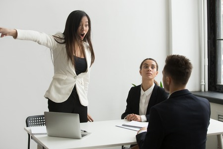 Furious stressed businesswoman angry at businessman telling to leave multi-ethnic meeting, asian executive firing dismissing shouting at male employee, bad interview, feminism and discrimination Stock Photo