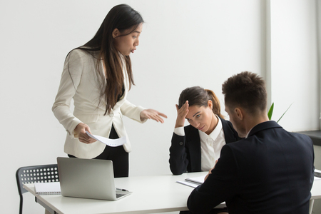 Angry asian executive shouting at subordinates scolding for bad results in report at diverse meeting, mad chinese female ceo boss leader dissatisfied with team incompetence reprimanding employees Archivio Fotografico - 102258717