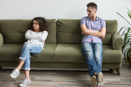 Frustrated millennial couple sit apart on couch in living room not talking after fight, unhappy boyfriend and girlfriend having disagreement thinking of bad relationships, marriage problems concept 版權商用圖片
