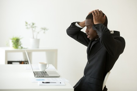 Shocked overwhelmed frustrated African American manager looking at laptop in despair, reading bad news about company business failure, bankruptcy and money loss. Concept of hopelessness, depression Stockfoto - 102258739
