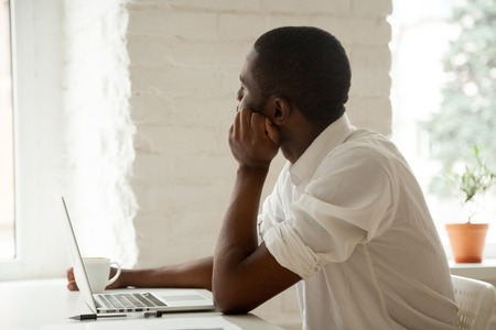 Thoughtful African American worker looking in window dreaming about future job achievements, developing new ideas, implementing successful projects, taking break from work, being lazy Stock Photo