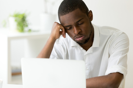 Tired disappointed male African American worker feeling exhausted, sitting in front of laptop, being lazy, suffering from sleep deprivation, falling asleep at workplace, boring work, no motivation