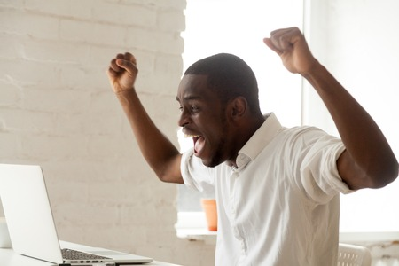 Excited amazed black worker throwing hands up, screaming celebrating online win, earning money, reaching goal, getting loan. Happy African American feeling euphoric after company business breakthrough Stock fotó