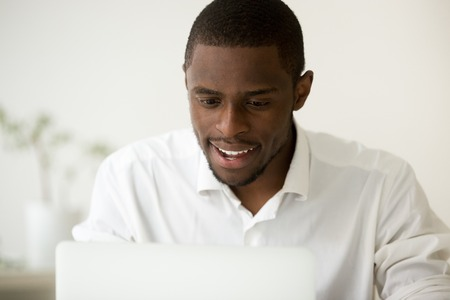 Excited happy African American manager looking at laptop screen, reading good company news online, knowing about raising profit positive statistics. Reward, result, online education concept. Portrait