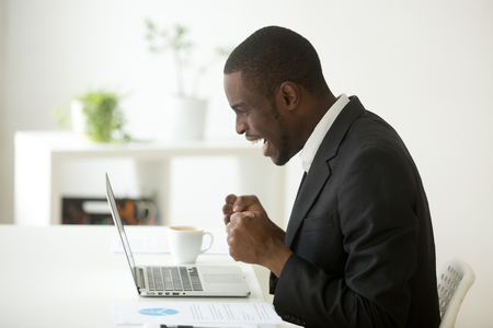 Excited African American manager making yes sign, looking at laptop reading great news about company business success, happy with online lottery win or getting job promotion, well done, reaching goal