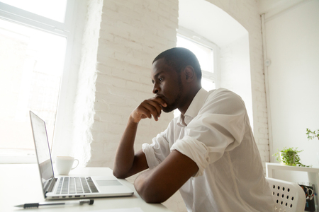 Focused thoughtful African American worker looking at laptop screen, heavily thinking about problem solution, analyzing possible variants, calculating risks, striving for business success motivation Stock Photo