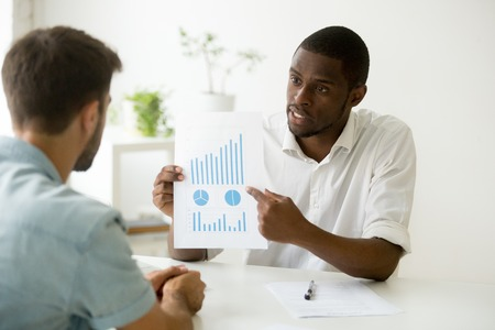 Serious casual worker showing presentation, explaining company financial market results. Two business colleagues or investors discussing diagrams, growing rates, investments, sales. Teamwork concept Stock Photo