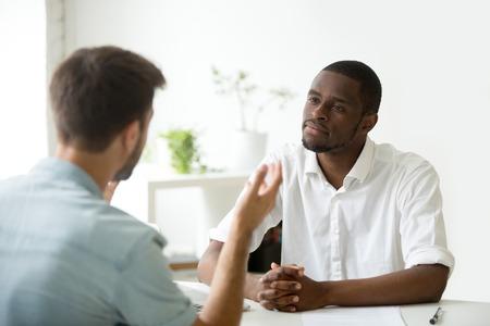 Datore di lavoro afroamericano che ascolta attentamente il candidato caucasico di lavoro che parla al colloquio di lavoro, essendo amichevole e interessato al candidato. Concetto di reclutamento, occupazione, assunzione