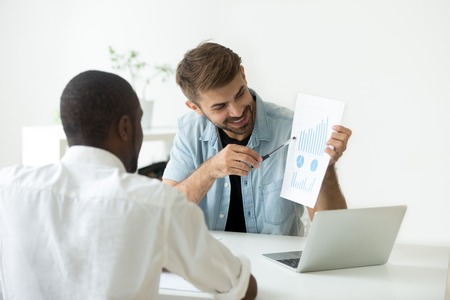Smiling Caucasian worker showing visual material to African American colleague, explaining diagrams, talking about investing, funds, growing sales stats, demonstrating successful business strategy