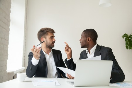 Mad African American worker arguing with Caucasian colleague about business contract, blaming coworker for documentation mistake. Diverse businessmen disagreeing at company meeting, customer complains