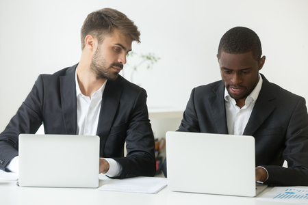 Curious Caucasian male businessman looking at screen of African American colleague busy working at laptop, worker glancing at rival computer, being smart, sly, cunning. Concept of rivalry cooperation
