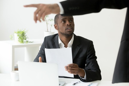 Frustrated shocked African American worker being fired, holding dismissal notice, while Caucasian employer pointing at door asking to leave. Concept of racial discrimination, employment termination Banco de Imagens