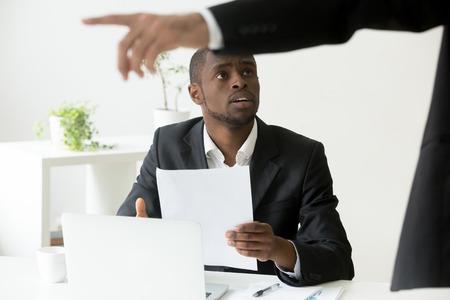 Gefrustreerde geschokte Afro-Amerikaanse werknemer die wordt ontslagen, met ontslagbevel, terwijl blanke werkgever naar de deur wijst en vraagt om te vertrekken. Concept van rassendiscriminatie, beëindiging van het dienstverband