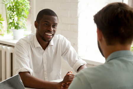 Smiling African American worker talking to colleague considering company work related issues, chatting on break, counseling, discussing latest news. Coworkers having casual conversation at workplace Banque d'images - 102284423