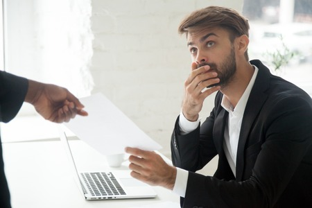 Frustrated shocked Caucasian male worker getting dismissal notice from African American boss asking to leave workplace. Employee receiving unexpected termination letter. Concept of firing, career end