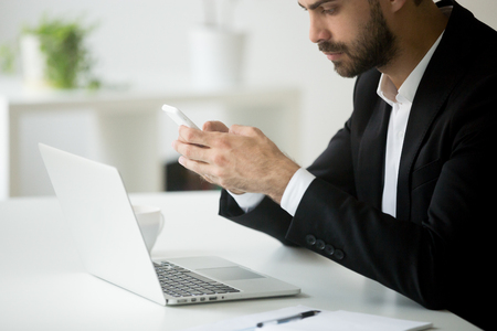 Businessman holding smartphone writing message working at laptop in office, typing business email on cellphone, texting to colleague, synchronizing cloud data. Concept of technology. Close up view Stok Fotoğraf