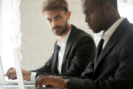 Suspicious cunning male Caucasian worker looking at serious working African American colleague, feeling mad and sneaky distrusting, having doubts, planning. Concept of office relationships, jealousy