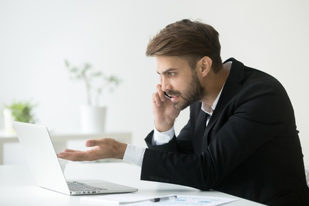 Irritated businessman talking over phone, working at laptop, solving company business problem, arguing. Angry manager speaking to technical support asking about computer or software malfunction Stock Photo