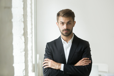 Headshot portrait of confident young caucasian businessman standing looking at camera, posing for commercial company photoshoot with arms crossed. Concept of leadership, success, ambition