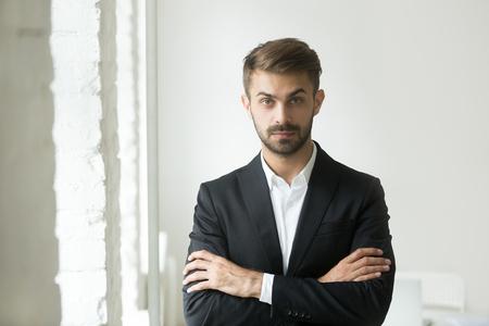 Kopfschussporträt des zuversichtlichen jungen kaukasischen Geschäftsmannes, der Kamera betrachtet und für Fotoshooting der kommerziellen Firma mit verschränkten Armen aufwirft. Konzept von Führung, Erfolg, Ehrgeiz