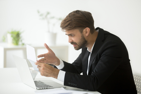 Mad frustrated businessman shocked by received letter, dissatisfied unhappy with contract conditions, disagree with information in business email, depressed with bad financial statistics and report