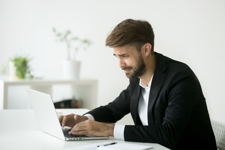 Stressed disappointed businessman worried about bad online news, reading about company financial crisis. Manager getting dismissal notice, receiving negative email