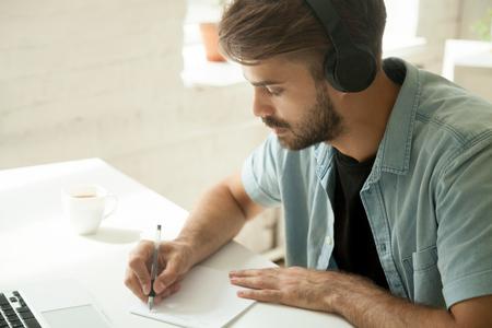 Skoncentrowany pracownik w słuchawkach oglądający seminarium internetowe przy laptopie, zapisujący ważne dane. Skoncentrowany student w słuchawkach biorący udział w kursie audio online, robiąc notatki, przygotowujący prezentację. Zamknąć widok
