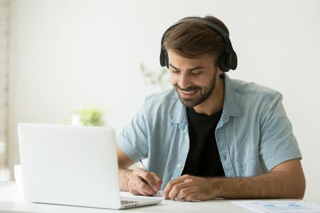 Hombre sonriente en auriculares viendo seminarios web, escuchando un curso de audio web, tomando notas y escribiendo información importante. Estudiante feliz disfrutando de la música mientras toma clases de e-learning, estudio remoto Foto de archivo